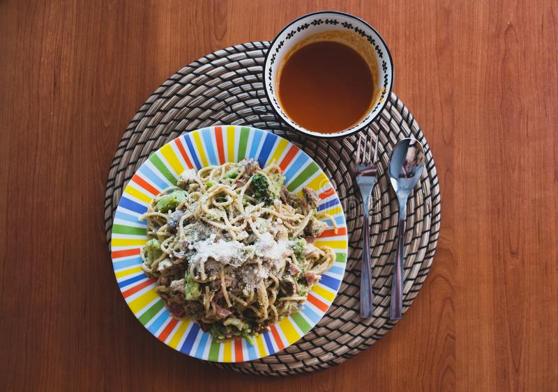 Μακαρόνια Carbonara στο ζωηρόχρωμο πιάτο και gazpacho στο κύπελλο όλοι στον ξύλινο πίνακα στοκ εικόνες