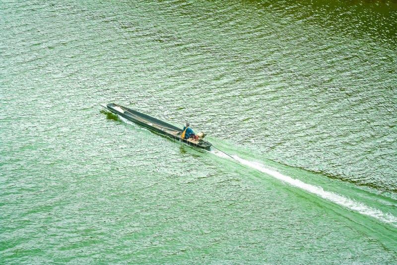 Μακριά βάρκα ουρών με το αλιεύοντας άτομο που πλέει με τον ποταμό, τοπ  στοκ εικόνα με δικαίωμα ελεύθερης χρήσης