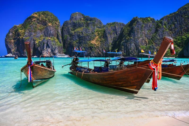 Μακριά βάρκα ουρών στην άσπρη παραλία άμμου με το κρύσταλλο - σαφής θάλασσα στοκ εικόνα με δικαίωμα ελεύθερης χρήσης