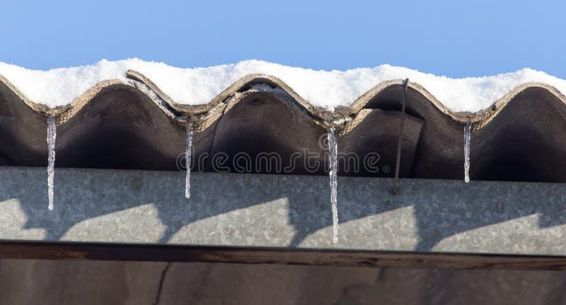 Μακριά και επικίνδυνα παγάκια σε μια στέγη σπιτιών στοκ εικόνες με δικαίωμα ελεύθερης χρήσης