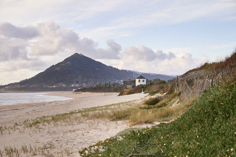 Μακριά παραλία μέχρι το λόφο, με έναν ανεμόμυλο στον αμμόλοφο στοκ εικόνες
