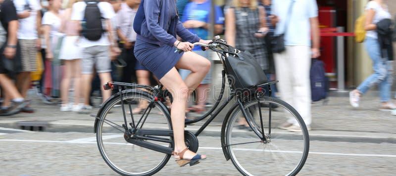 Μακριά πόδια της γυναίκας ενώ γρήγορο πεντάλι στο ποδήλατο και το backgroun στοκ εικόνες