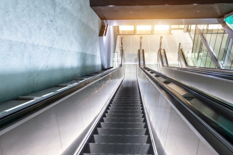 Μακριά σκάλα κυλιόμενων σκαλών που κατεβαίνει στον υπόγειο, υποδομή αστικών μεταφορών στοκ εικόνες