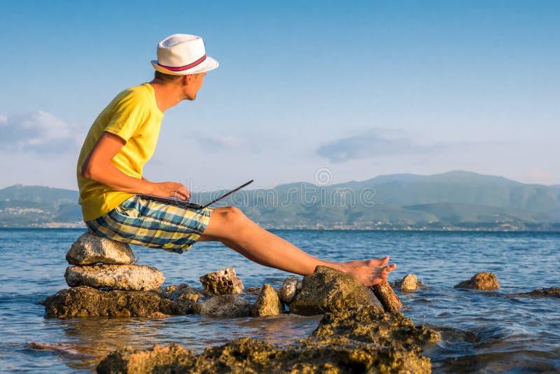 Μακρινή εργασία οπουδήποτε Καθιστώντας τα χρήματα σε απευθείας σύνδεση καθμένος στο βράχο κοντά στον ωκεανό θάλασσας Ηλεκτρονικά  στοκ φωτογραφίες με δικαίωμα ελεύθερης χρήσης