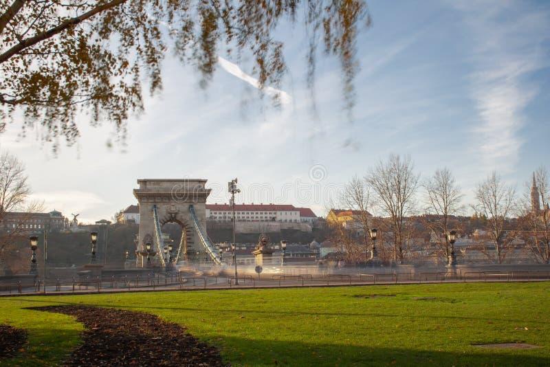 Μακροχρόνια έκθεση στην ηλιοφάνεια Τα αυτοκίνητα οδηγούν γρήγορα πέρα από τη γέφυρα αλυσίδων στις τράπεζες του Δούναβη στη Βουδαπ στοκ φωτογραφίες με δικαίωμα ελεύθερης χρήσης