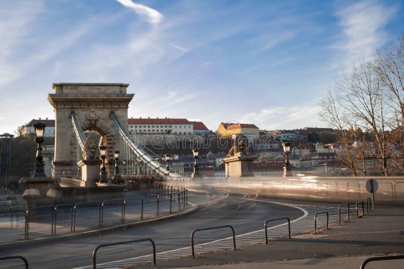 Μακροχρόνια έκθεση στην ηλιοφάνεια Τα αυτοκίνητα οδηγούν γρήγορα πέρα από τη γέφυρα αλυσίδων στις τράπεζες του Δούναβη στη Βουδαπ στοκ εικόνες με δικαίωμα ελεύθερης χρήσης
