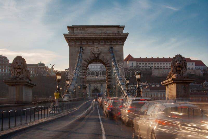 Μακροχρόνια έκθεση στην ηλιοφάνεια Τα αυτοκίνητα οδηγούν γρήγορα πέρα από τη γέφυρα αλυσίδων στις τράπεζες του Δούναβη στη Βουδαπ στοκ εικόνες