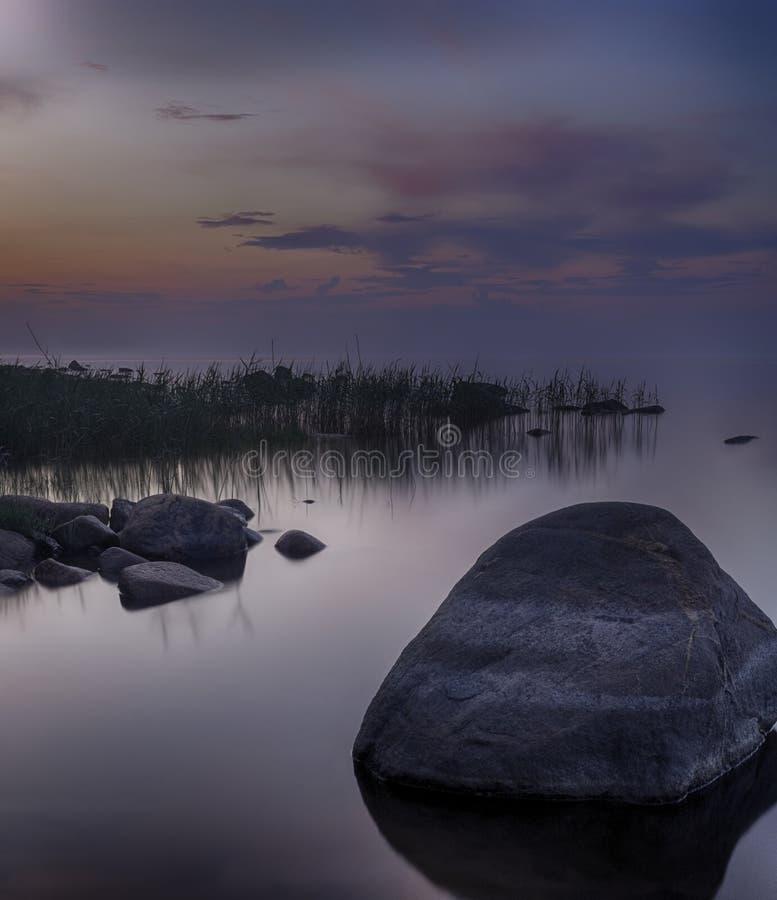 Μακροχρόνια έκθεση του ηλιοβασιλέματος στη Ladoga λίμνη Όμορφο scape με την παραλία, τους καλάμους και το νερό πετρών Ladoga λίμν στοκ εικόνες με δικαίωμα ελεύθερης χρήσης
