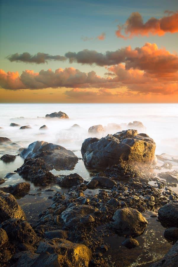 Μακροχρόνια έκθεση Waterscape στο σημείο Ka'Ena, Χαβάη, κατά τη διάρκεια του ηλιοβασιλέματος στοκ εικόνες