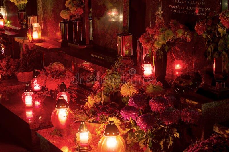 Μακροχρόνια εικόνα νύχτας έκθεσης HDR των διακοσμήσεων και των κεριών που καίνε στον τάφο σε ένα νεκροταφείο κατά τη διάρκεια όλη στοκ εικόνες