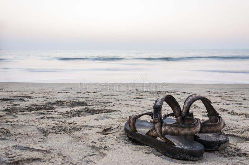 Μακροχρόνια πηγή σανδαλιών έκθεσης στην παραλία άμμου στο ηλιοβασίλεμα στοκ εικόνες
