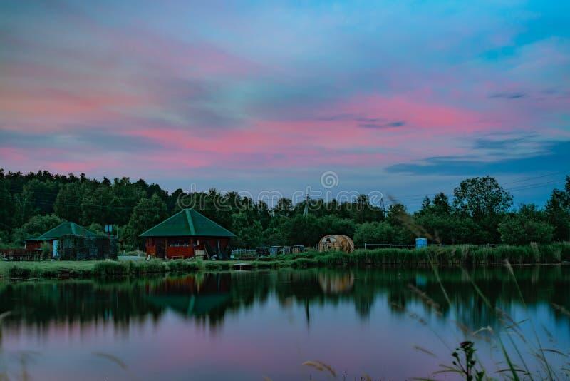 Μακροχρόνια φυσική άποψη έκθεσης του μικρού κόκκινου σπιτιού στην τράπεζα ακόμα της λίμνης στοκ φωτογραφία