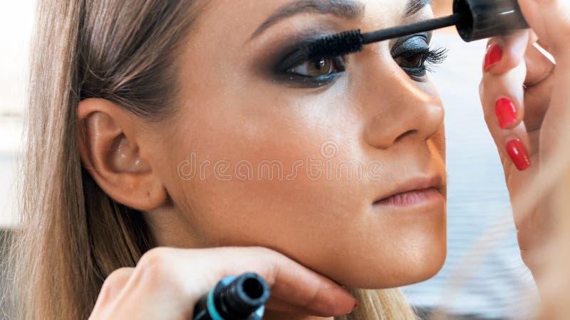 Μακρο εικόνα του καλλιτέχνη makeup που χρωματίζει τα πρότυπα μάτια ` s με mascara στοκ φωτογραφίες