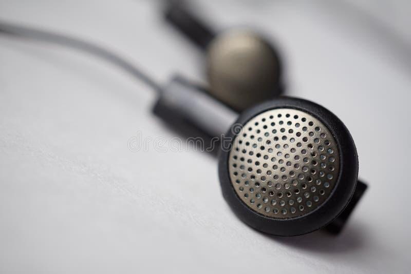 Μακρο λεπτομέρεια ασημένια και μαύρα διατρυπημένα ακουστικά (αυτί-οφθαλμοί) με τα καλώδια στοκ εικόνες με δικαίωμα ελεύθερης χρήσης