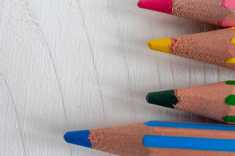 Μακρο κινηματογράφηση σε πρώτο πλάνο διάφορων χρωματισμένων μολυβιών για το σχολείο, οριζόντια στο άσπρο ξύλο στοκ φωτογραφία