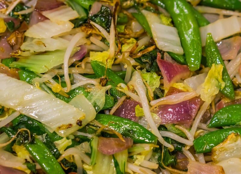 Μακρο κινηματογράφηση σε πρώτο πλάνο ενός μαγειρευμένου ασιατικού φυτικού μίγματος, υγιές vegan υπόβαθρο τροφίμων στοκ εικόνα