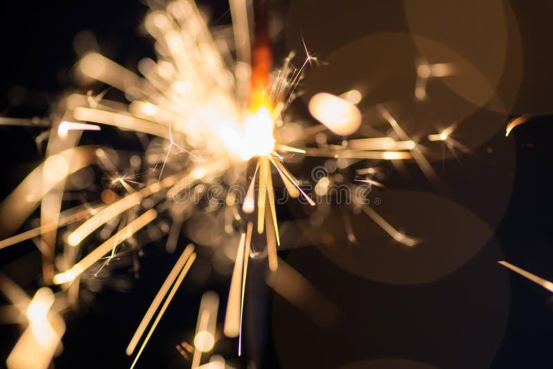 Μακρο κινηματογράφηση σε πρώτο πλάνο του υποβάθρου sparkler τη νύχτα - που θολώνεται για το effe στοκ φωτογραφία