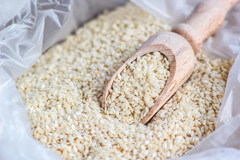 Μακρο φωτογραφία των οργανικών φυσικών άσπρων σπόρων σουσαμιού στο ξύλινο κουτάλι στην άσπρη πλαστική τσάντα αγορών κοντά επάνω Φ στοκ φωτογραφίες