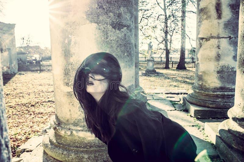 Μακρυμάλλες κορίτσι με το τρομακτικό makeup στο παλαιό υπόβαθρο εκκλησιών στοκ φωτογραφία