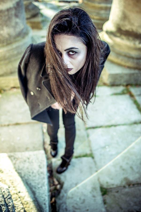 Μακρυμάλλες κορίτσι με το τρομακτικό makeup στο παλαιό υπόβαθρο εκκλησιών στοκ φωτογραφίες με δικαίωμα ελεύθερης χρήσης