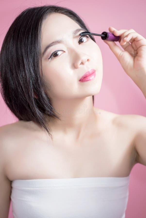 Μακρυμάλλης ασιατική νέα όμορφη γυναίκα που εφαρμόζει mascara που απομονώνεται πέρα από το ρόδινο υπόβαθρο φυσικό makeup, θεραπεί στοκ εικόνα