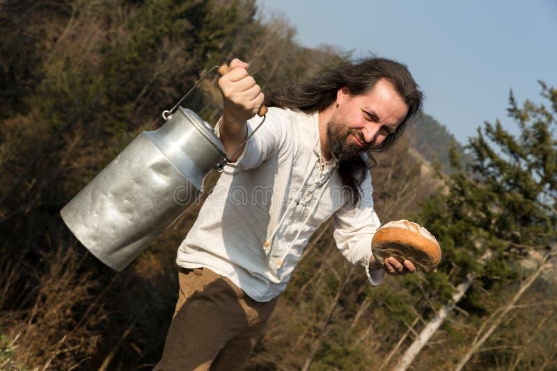 Μακρυμάλλης καλλιεργητής που προσφέρει ένα καρδάρι γάλακτος και ένα ψωμί στοκ φωτογραφία με δικαίωμα ελεύθερης χρήσης