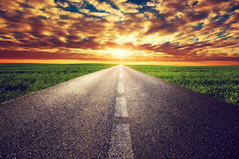 Μακρύς ευθύς δρόμος, τρόπος προς τον ήλιο ηλιοβασιλέματος στοκ φωτογραφία με δικαίωμα ελεύθερης χρήσης