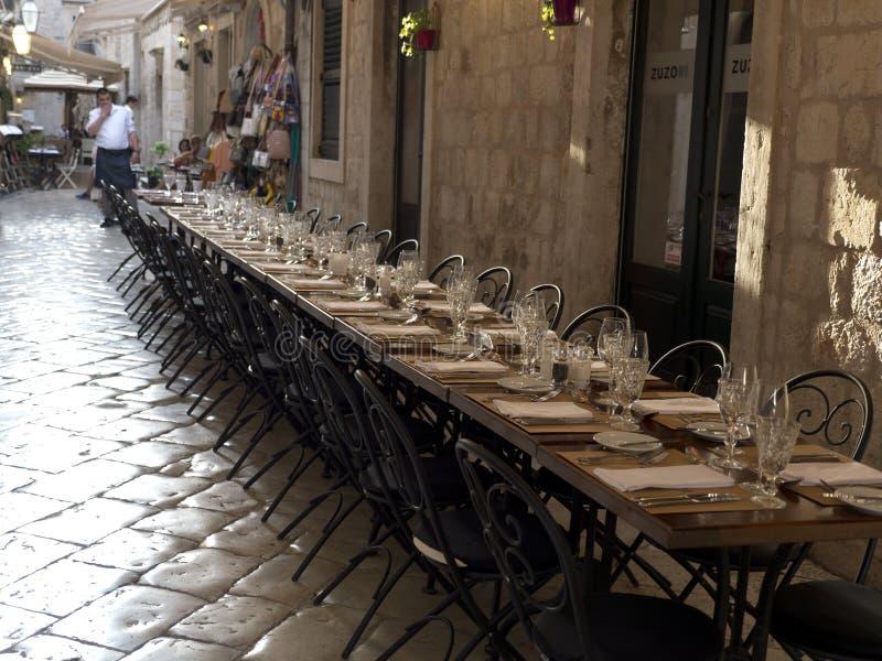 Μακρύς πίνακας για τους φιλοξενουμένους, παλαιά πόλη Dubrovnik με το πεζοδρόμιο πετρών στοκ φωτογραφία με δικαίωμα ελεύθερης χρήσης
