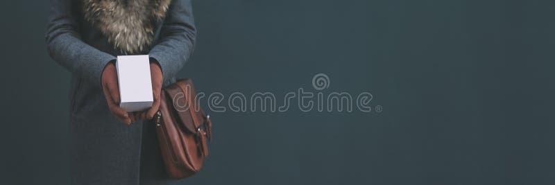 Μακρύ έμβλημα με τη χλεύη επάνω ένα άσπρο κιβώτιο από ένα smartphone Το κορίτσι σε ένα παλτό και καφετιά γάντια κρατά ένα δώρο στ στοκ φωτογραφία με δικαίωμα ελεύθερης χρήσης