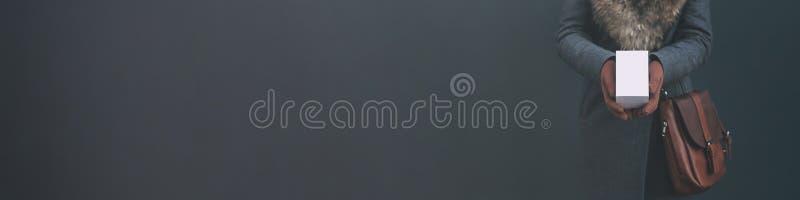 Μακρύ έμβλημα με τη χλεύη επάνω ένα άσπρο κιβώτιο από ένα smartphone Το κορίτσι σε ένα παλτό και καφετιά γάντια κρατά ένα δώρο στ στοκ φωτογραφίες
