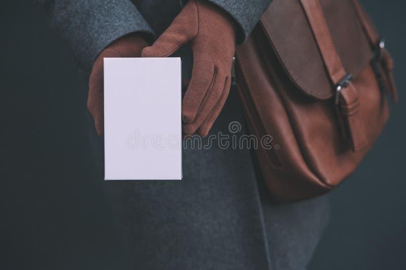 Μακρύ έμβλημα με τη χλεύη επάνω ένα άσπρο κιβώτιο από ένα smartphone Το κορίτσι σε ένα παλτό και καφετιά γάντια κρατά ένα δώρο στ στοκ εικόνα με δικαίωμα ελεύθερης χρήσης