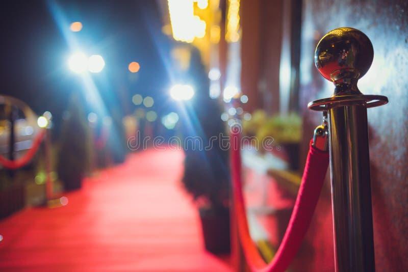 Μακρύ κόκκινο χαλί μεταξύ των εμποδίων σχοινιών στην είσοδο στοκ φωτογραφίες