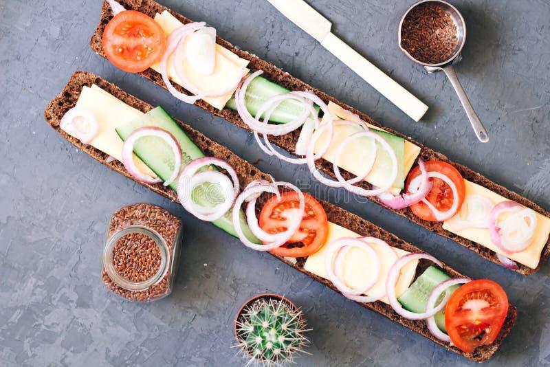 Μακρύ φλοιώδες baguette θερμό, πρόσφατα ψημένο σίκαλη ψωμί με το τυρί, αγγούρι και ντομάτες με τα κρεμμύδια σε έναν αγροτικό στοκ φωτογραφίες