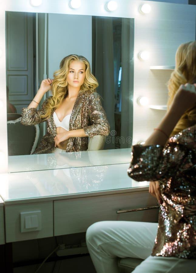 Μακρύ φόρεμα τρίχας Hollywood Πίσω, πλάγια όψη Νέο ελκυστικό κορίτσι με τα σγουρά μακριά ξανθά μαλλιά σε ένα χρυσό λαμπρό σακάκι  στοκ εικόνα