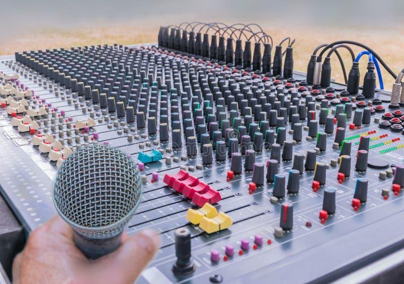 Μαλακή θολωμένη και μαλακή εστίαση του μικροφώνου με τους ελέγχους του ήχου που αναμιγνύει την κονσόλα, ήχος αναμικτών στοκ φωτογραφία
