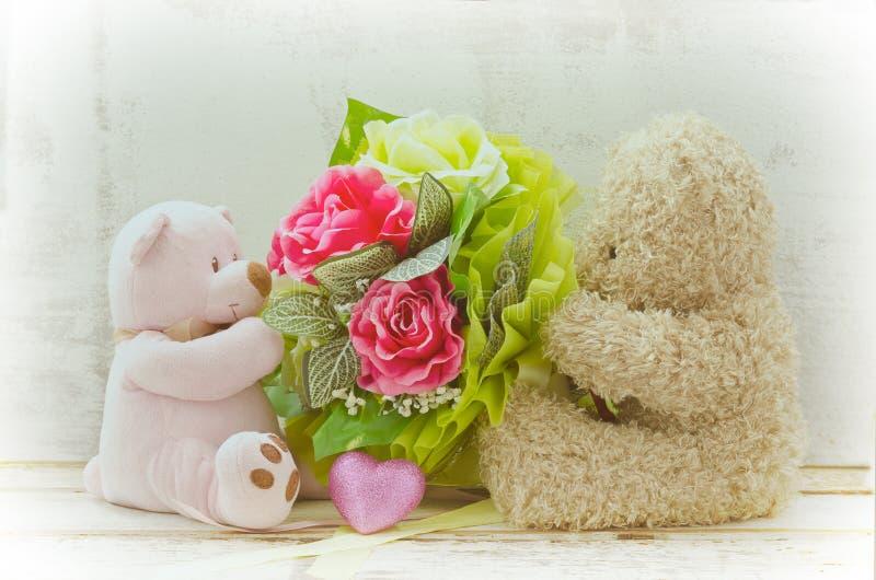 Μαλακό ζεύγος εστίασης των χαριτωμένων αρκούδων που κρατά την ανθοδέσμη τριαντάφυλλων στοκ φωτογραφίες