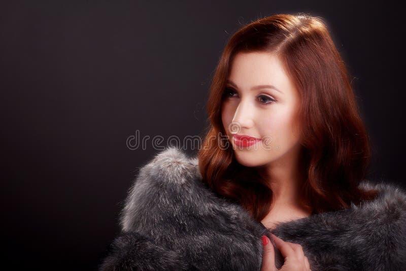 Μαλακό πορτρέτο εστίασης της όμορφης νέας γυναίκας που φορά ένα παλτό γουνών στοκ εικόνες