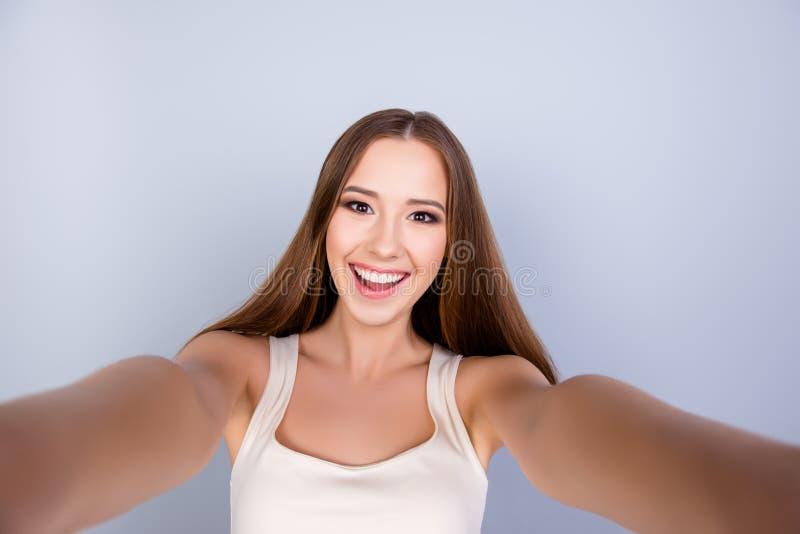 Μανία Selfie! Το χαριτωμένο νέο κορίτσι με ένα ακτινοβολώντας χαμόγελο παίρνει το s στοκ φωτογραφία