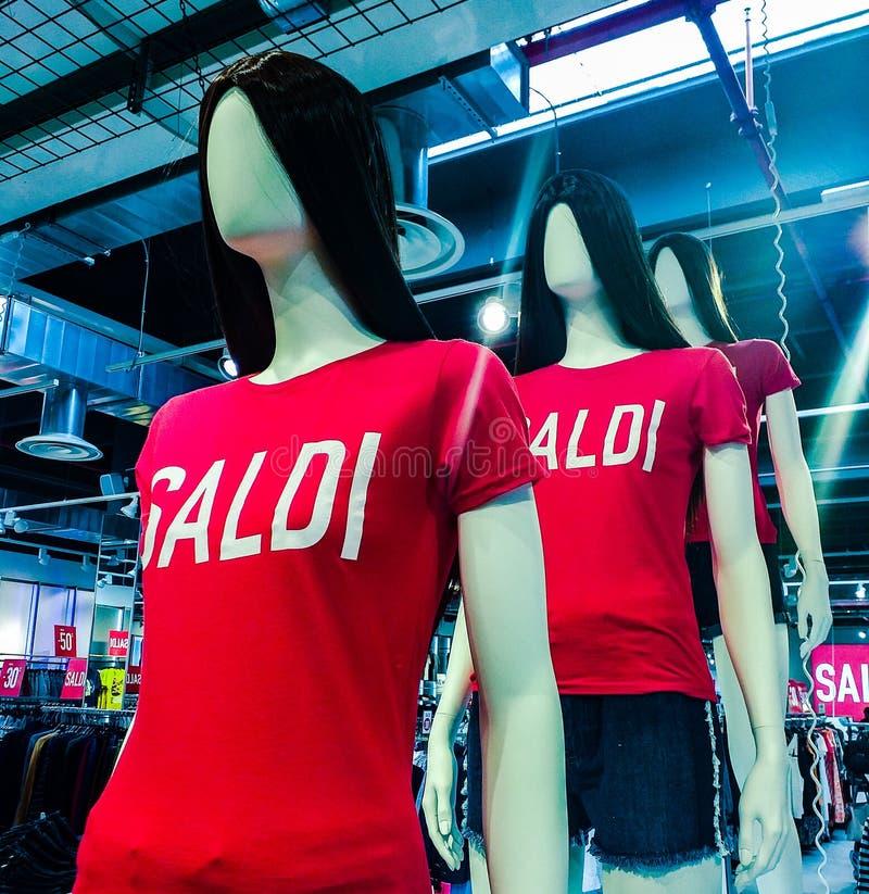 Μανεκέν στα καταστήματα που φορούν σε ένα όμορφο πουκάμισο με τις πωλήσεις λέξης στοκ φωτογραφίες
