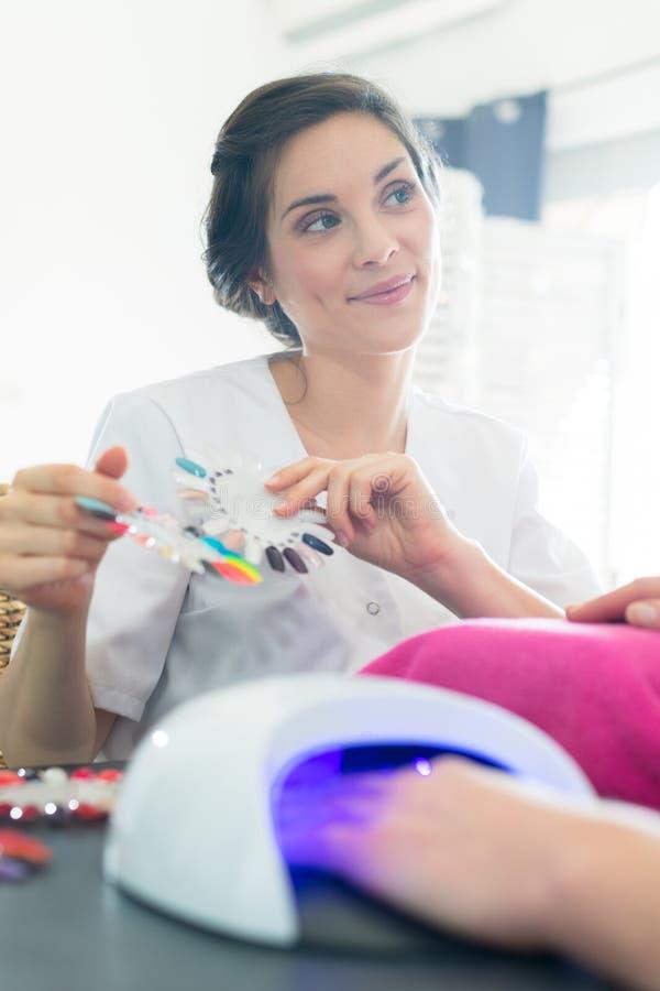 Μανικιουρίστρια που δείχνει επιλογές για επέκταση νυχιών στοκ φωτογραφίες