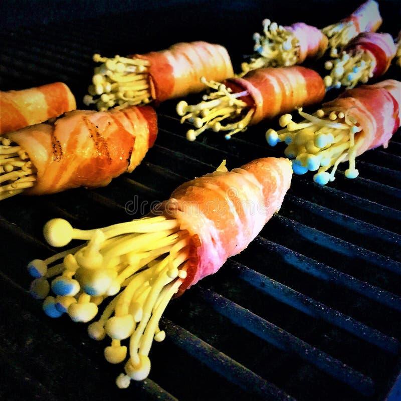 Μανιτάρια Enoki που τυλίγονται στο μπέϊκον στη σχάρα στοκ εικόνες