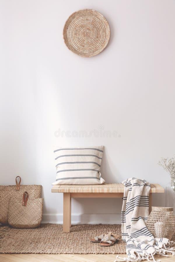 Μαξιλάρι και κάλυμμα στο ξύλινο σκαμνί στο άσπρο εσωτερικό καθιστικών με το καφετί πιάτο Πραγματική φωτογραφία στοκ εικόνα