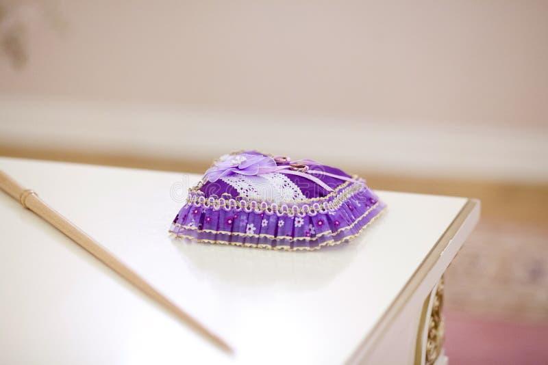 Μαξιλάρι με τα γαμήλια δαχτυλίδια στον πίνακα στοκ φωτογραφία με δικαίωμα ελεύθερης χρήσης