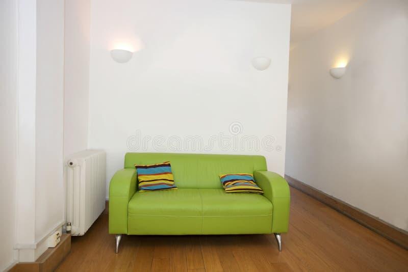 Μαξιλάρια στον πράσινο καναπέ στο κενό γραφείο στοκ εικόνα με δικαίωμα ελεύθερης χρήσης
