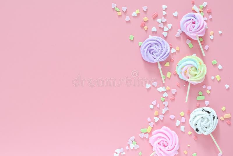 Μαρέγκες στα χρώματα κρητιδογραφιών και διεσπαρμένος ζωηρόχρωμος στο ρόδινο υπόβαθρο στοκ φωτογραφία με δικαίωμα ελεύθερης χρήσης