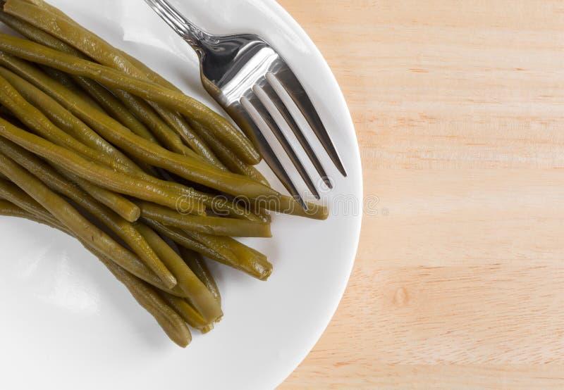 Μαριναρισμένα πράσινα φασόλια σε ένα πιάτο με το δίκρανο στοκ φωτογραφίες