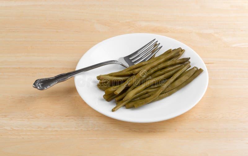 Μαριναρισμένα πράσινα φασόλια σε ένα πιάτο με το δίκρανο στοκ φωτογραφία με δικαίωμα ελεύθερης χρήσης