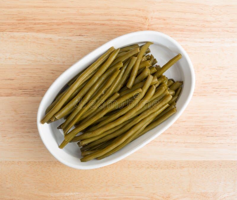 Μαριναρισμένα πράσινα φασόλια σε ένα πιάτο ψησίματος στοκ φωτογραφίες