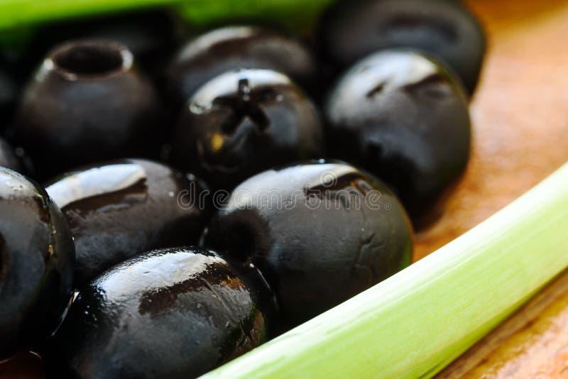 Μαριναρισμένες μαύρες ελιές στο ξύλινο υπόβαθρο στοκ εικόνα με δικαίωμα ελεύθερης χρήσης