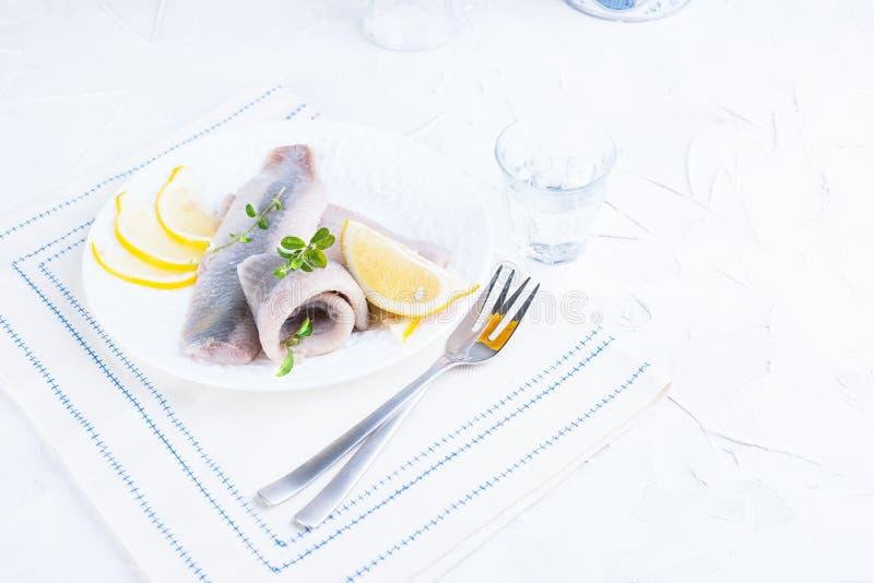 Μαριναρισμένη λωρίδα ρεγγών σε ένα άσπρο πιάτο με το λεμόνι και το κρεμμύδι Εξυπηρετούμενος πίνακας και η παραδοσιακή λιχουδιά άν στοκ εικόνα